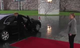 Embattled PM gets stuck in her car as she arrives for Merkel talks