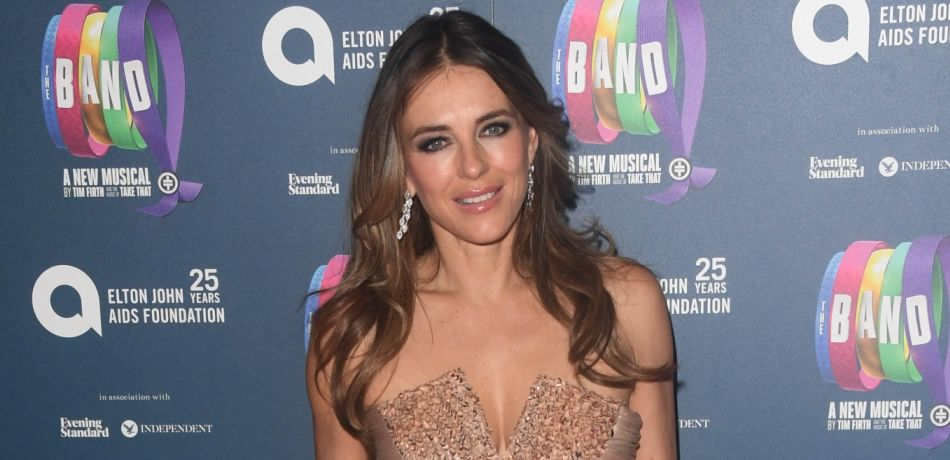 British Beauty Elizabeth Hurley Flirts With Deep Cleavage, Bare Thighs In Elegant White Dress