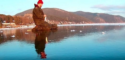 Moment explorer tiptoes across ice covering world's deepest lake
