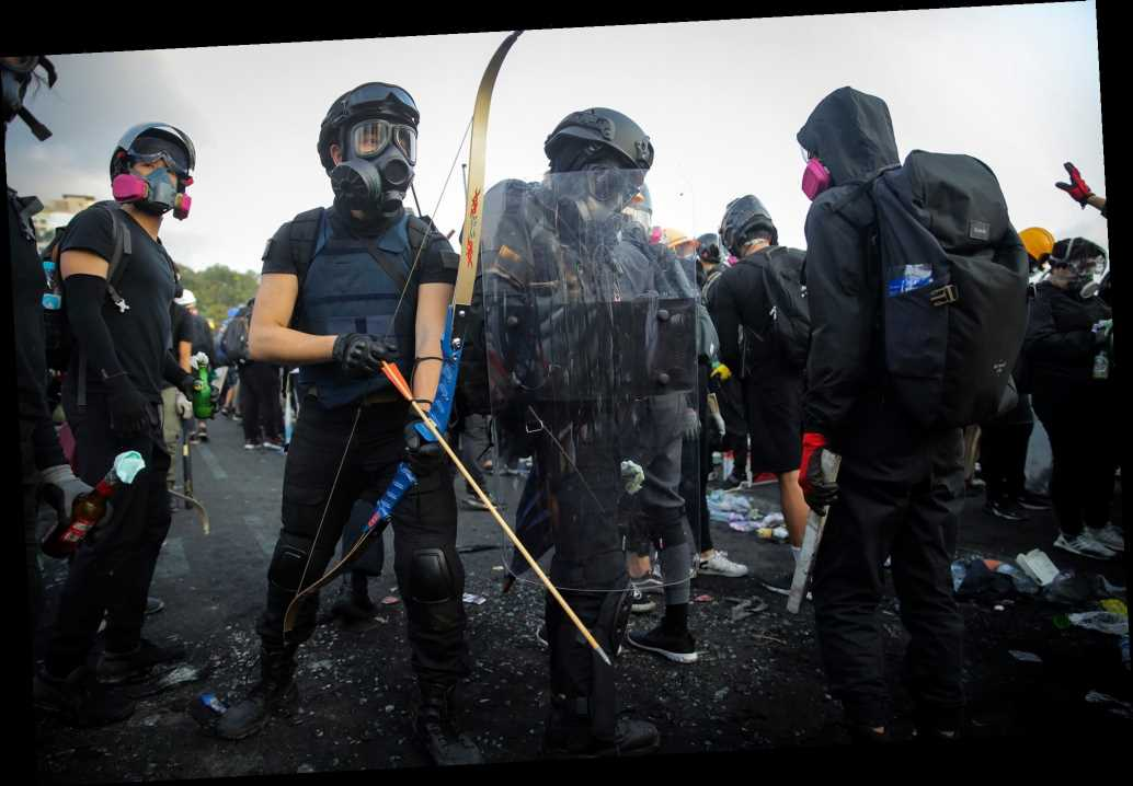 Hong Kong protesters fire arrows, javelins and tear gas against armed riot police