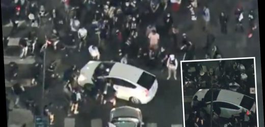 Dramatic moment car is CHASED by huge mob of protesters who 'smash a window' as the vehicle drives through crowd