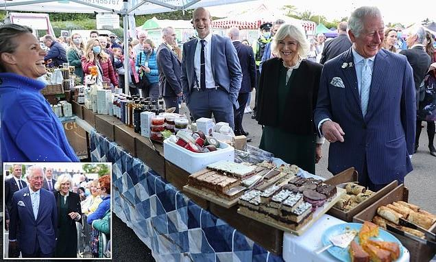Prince Charles looks cheerful as he jokes with street vendors