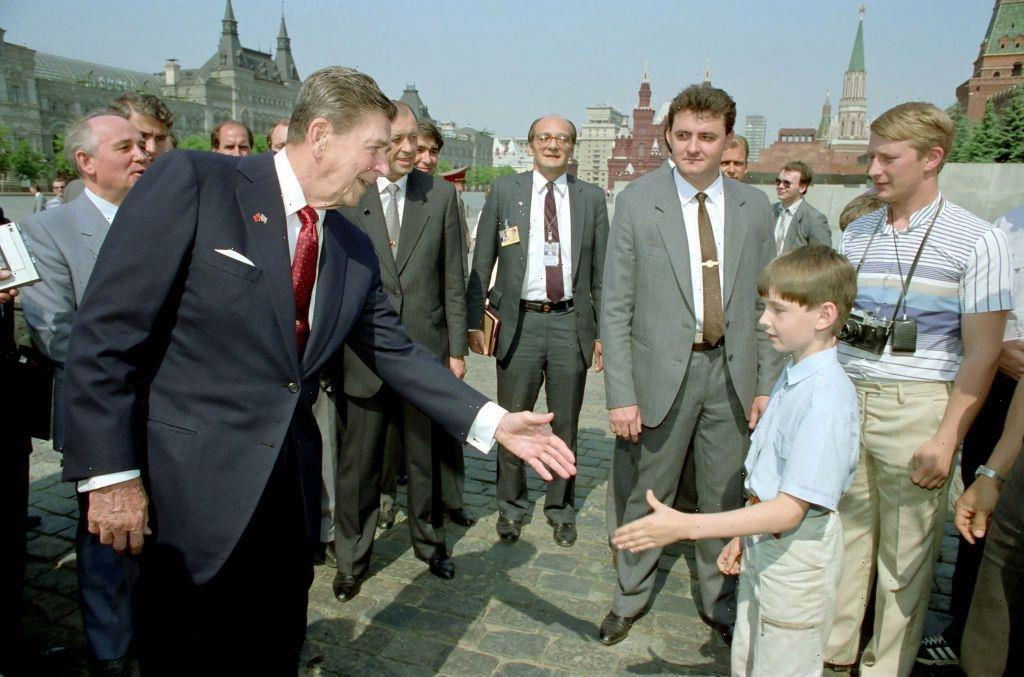 Conspiracy theorists convinced PUTIN is camera-holding tourist in 1988 pic of Reagan meeting boy in Moscow