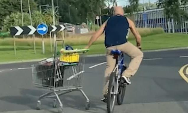 Cyclist wheels shopping trolley along road before it crashes