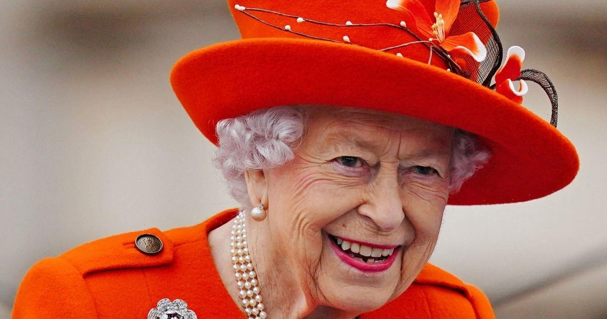 The Queen dons bright orange ensemble for engagement at Buckingham Palace